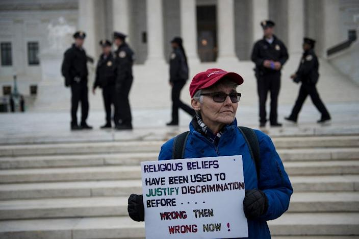A supporter of the same-sex couple who sued a baker over a wedding cake holds a sign outside the Supreme Court (AFP Photo/Brendan Smialowski)