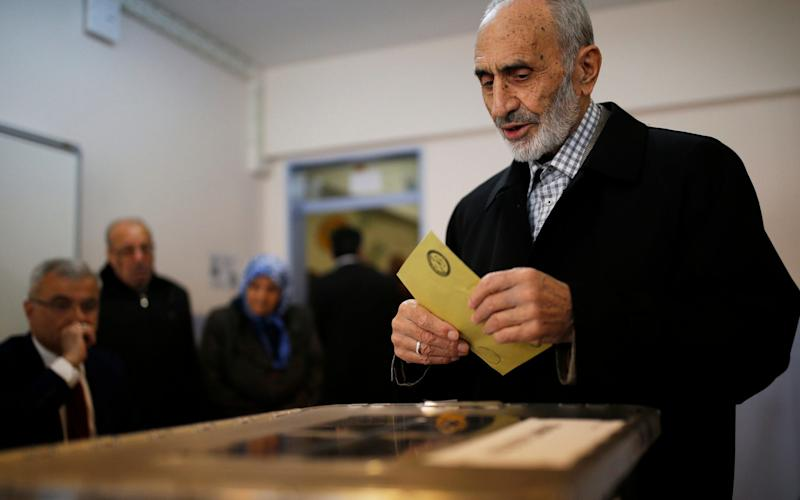 A voter prepares to cast a ballot inside a polling station in Istanbul - Credit: AP Photo/Emrah Gurel