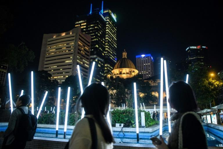 People walk past French artist Christophe Mayer's 'Bamboo Square' installation in Statue Square Gardens during the opening of Lumieres Hong Kong in the city's Central district