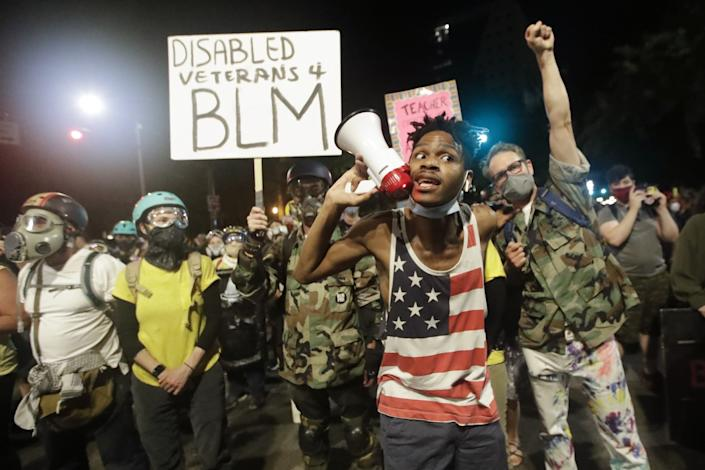 A protester shouts into a bullhorn next to a group of military veterans with a Disabled Veterans 4 BLM sign