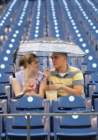Sarah, left, and Anthony Nguyen find shelter from the rain before a baseball game between the Philadelphia Phillies and the St Louis Cardinals, Saturday, Aug. 23, 2014, in Philadelphia. (AP Photo/Laurence Kesterson)