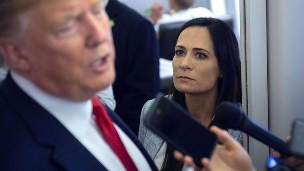 PHOTO: White House Press Secretary Stephanie Grisham listens as President Donald Trump speaks to the media aboard Air Force One while flying between El Paso, Texas and Joint Base Andrews in Md., Aug. 7, 2019. (Saul Loeb/AFP/Getty Images, FILE)