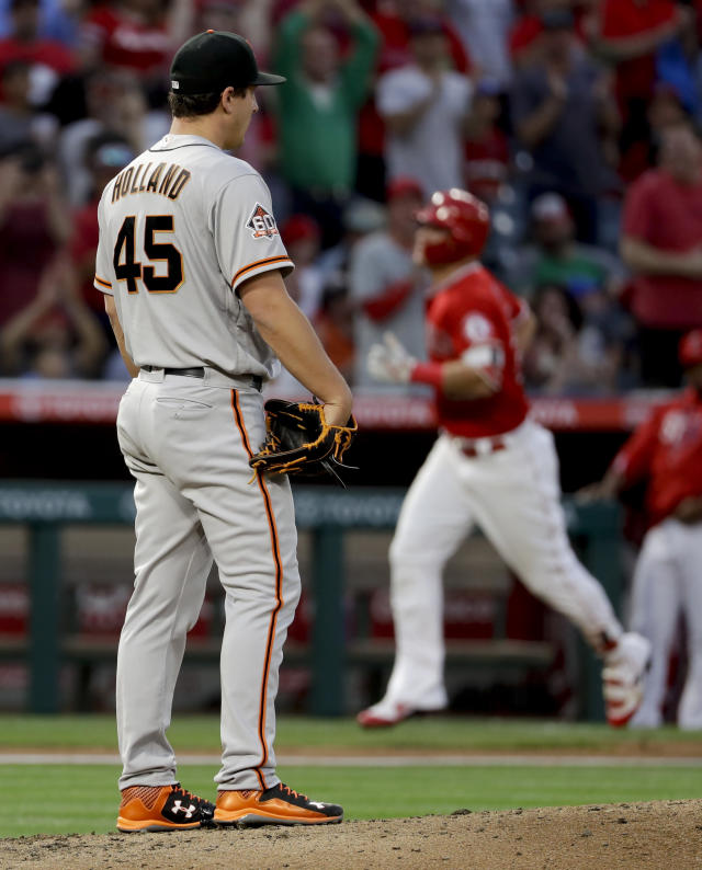 San Francisco Giants starting pitcher Derek Holland, left, watches as Los Angeles Angels' Mike Trout rounds the bases after a home run during the third inning of a baseball game in Anaheim, Calif., Saturday, April 21, 2018. (AP Photo/Chris Carlson)
