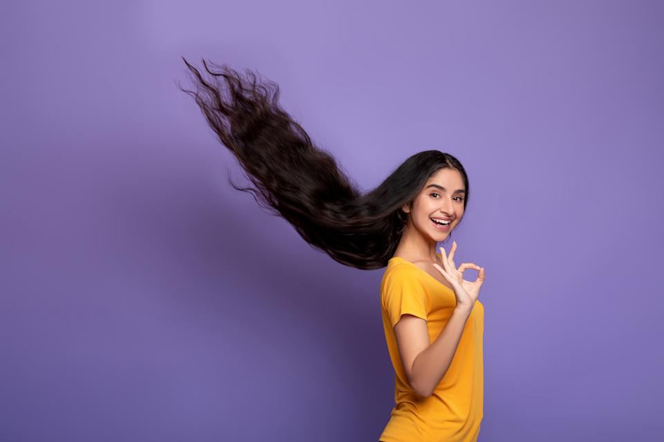 Hair Care Concept. Portrait of smiling indian model woman posing with long flying hair and showing okay sign gesture. Beautiful young lady standing isolated over purple studio background, copy space
