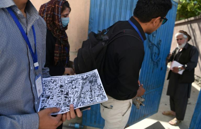 Afghan surveyors from the UN-Habitat team go door to door as to register unregulated houses in Kabul
