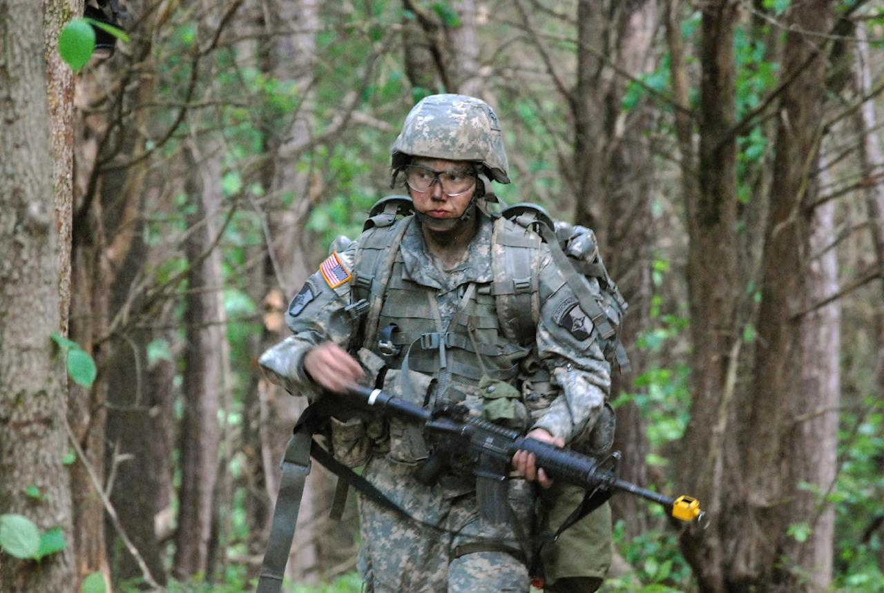 In a May 9, 2012 photo, Capt. Sara Rodriguez of the 101st Airborne Division walks through the woods during the expert field medical badge testing at Fort Campbell, Ky., on May 9, 2012. Female soldiers are moving into new jobs in once all-male units as the U.S. Army breaks down formal barriers in recognition of what's already happened in wars in Iraq and Afghanistan. (AP Photo/Kristin M. Hall)