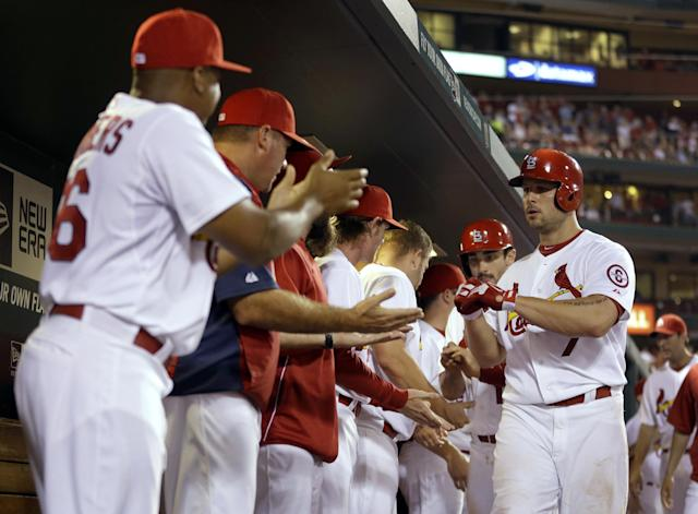 St. Louis Cardinals' Matt Holliday, right, is congratulated by teammates in the dugout after hitting a two-run home run during the sixth inning of a baseball game against the Milwaukee Brewers on Tuesday, Sept. 10, 2013, in St. Louis. (AP Photo/Jeff Roberson)
