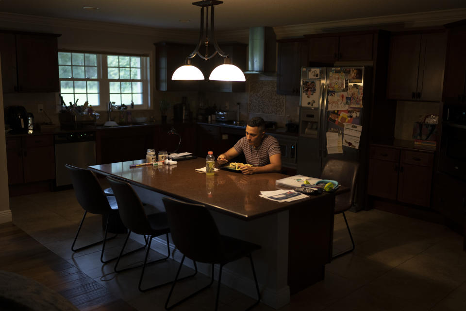 Luis Puertas has dinner in his home in Orlando, Fla., on Sunday, Aug. 8, 2021. His 7-year-old daughter, who he loves so much it almost hurts, only lives with him part-time. His relationship with her mother turned bad long ago. Much of his family lives far away. (AP Photo/Emilio Morenatti)