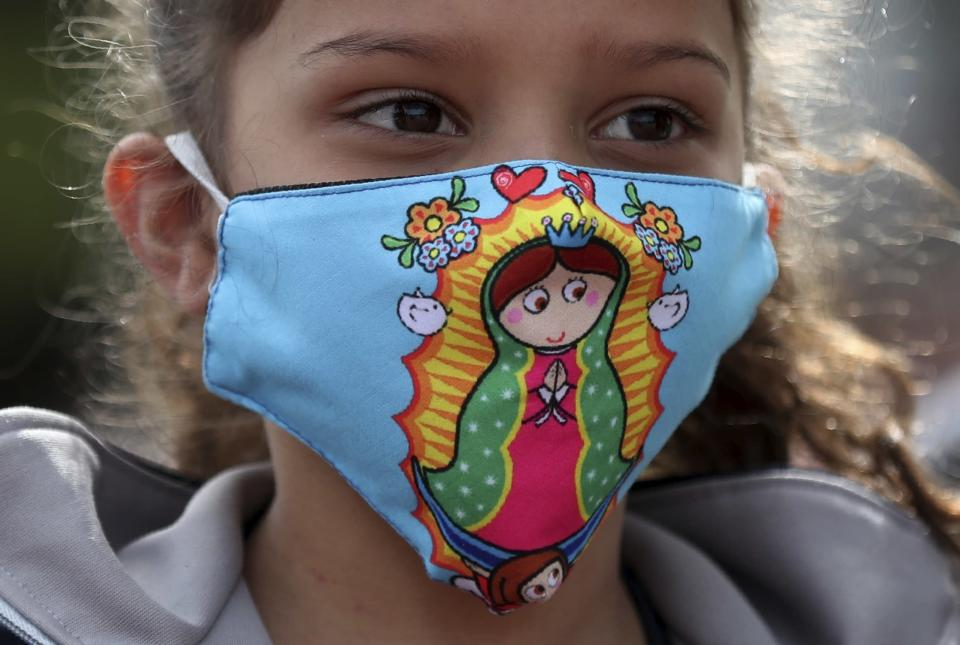 A Venezuelan migrant girl, wearing a protective face mask with a graphic version of the Virgin of Guadalupe, waits for a bus to travel to the border, after breaking camp in Bogota, Colombia, Thursday, July 2, 2020. Facing no work due to the COVID-19-related economic shutdown, hundreds of Venezuelan migrants are returning to their country. (AP Photo/Fernando Vergara)