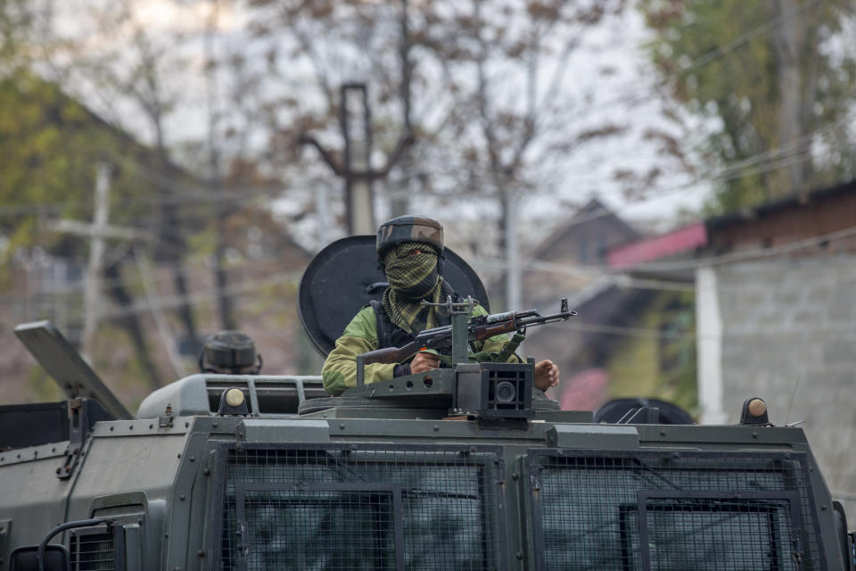 An Indian army soldier stands guard atop an armored vehicle near the site of a gun battle on the outskirts of Srinagar, Indian controlled Kashmir, Sunday, Nov. 1, 2020. According to police, Indian government forces killed Saifullah Mir, a top rebel commander of the region's largest rebel group, Hizbul Mujahideen which has spearheaded an armed rebellion against Indian rule for decades. (AP Photo/ Dar Yasin)