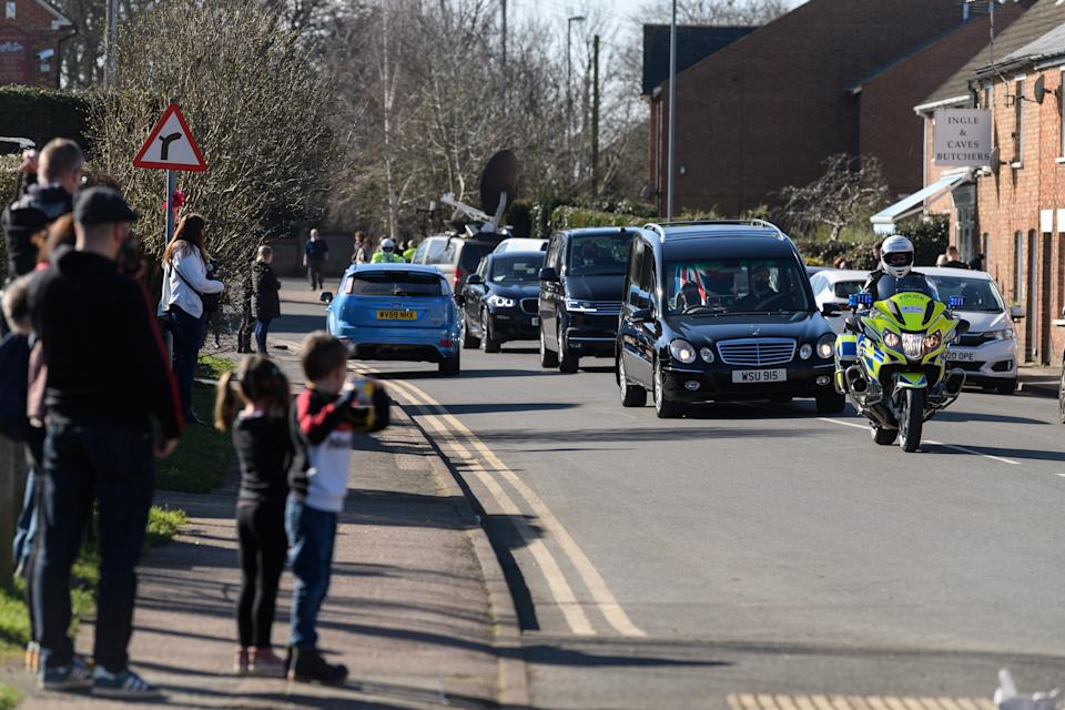 BEDFORD, ENGLAND - FEBRUARY 27: The funeral procession for Sir Tom Moore passes through the village of Marston Moretaine on the way to Bedford Crematorium ahead of a private ceremony on February 27, 2021 in Bedford, England. WWII veteran, Sir Tom raised nearly £33 million for NHS charities ahead of his 100th birthday last year by walking laps of his garden in Marston Moretaine, Bedfordshire. He died on the 2nd of February after testing positive for COVID-19. (Photo by Leon Neal/Getty Images)