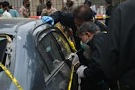 Members of Police Crime Scene Unit investigate around a car used by alleged gunmen at the main entrance of the Pakistan Stock Exchange building in Karachi on June 29, 2020. - At least six people were killed when gunmen attacked the Pakistan Stock Exchange in Karachi on June 29, with a policeman among the dead after the assailants opened fire and hurled a grenade at the trading floor, police said. (Photo by Rizwan TABASSUM / AFP) (Photo by RIZWAN TABASSUM/AFP via Getty Images)