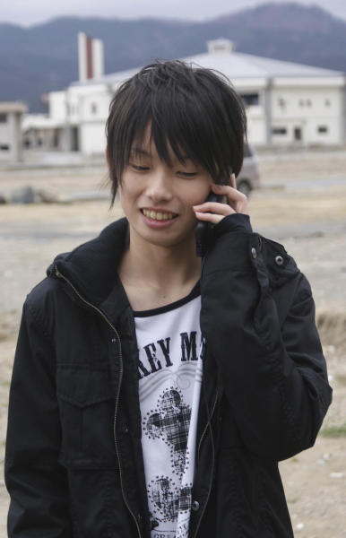 In this April 22, 2012 photo, Misaki Murakami stands where his home, which was washed away by the March 11, 2011 tsunami, once stood, while talking on a mobile phone with David Baxter in Alaska, U.S., in Rikuzentakata, Iwate Prefecture, northern Japan. Baxter found Murakami's soccer ball, which was lost in last year's tsunami, on a remote Alaskan island. (AP Photos/Sankei Shimbun, Yoko Watanabe) JAPAN OUT, MANDATORY CREDIT, NO SALES