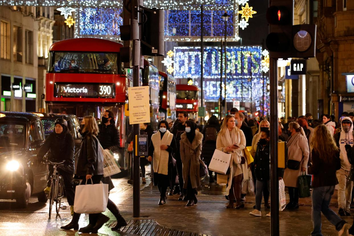 """Shoppers and pedestrians pass under the Christmas lights on Oxford Street in central London on December 14, 2020, as it is announced that Greater London will be moved into Tier 3 from Tier 2 from Wednesday December 16. - London is to move into the highest level of anti-virus restrictions, the health minister announced Monday. The British capital from Wednesday will go into """"tier three"""" restrictions, which force the closure of theatres and ban people from eating out at restaurants or drinking in pubs, the Health Secretary Matt Hancock told parliament. (Photo by Tolga Akmen / AFP) (Photo by TOLGA AKMEN/AFP via Getty Images)"""