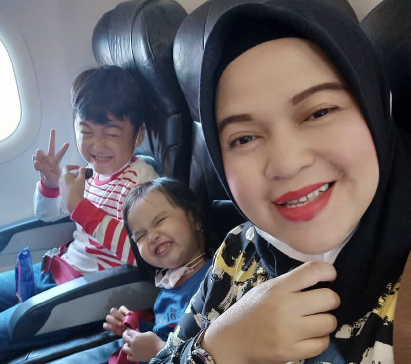 Ratih Windania pictured on board a flight with two children.