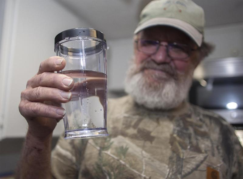 "Flemington Road community member Sam Malpass of Wilmington, N.C. holds a glass of water from his home on Wednesday, Feb. 19, 2014. Malpass and his wife Pat are part of a small community near L.V. Sutton Complex operated by Duke Energy they feel could be polluting well water with spill off and seepage from large coal ash ponds. ""If you want to know what it's like living near a coal ash pond, this is it,"" said Malpass, 67, a retired carpenter and Vietnam veteran. ""We're afraid to drink the water because we don't know what's in it. We can't eat the fish because we don't know if it's safe anymore. It's changed our lives out here."" (AP Photo/Randall Hill)"