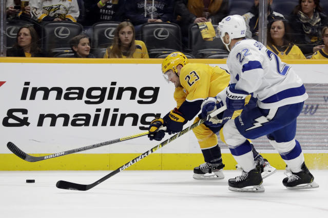 Nashville Predators right wing Rocco Grimaldi (23) moves the puck against Tampa Bay Lightning defenseman Kevin Shattenkirk (22) in the second period of an NHL hockey game Tuesday, Dec. 3, 2019, in Nashville, Tenn. (AP Photo/Mark Humphrey)