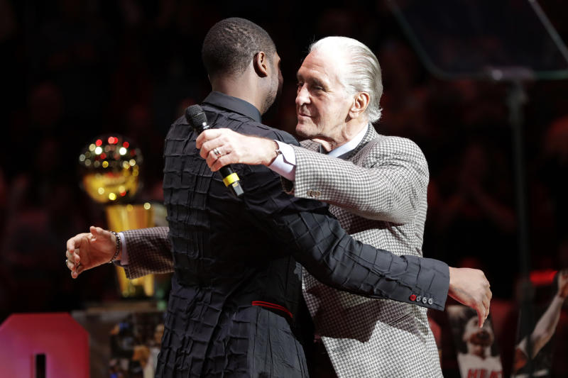 Former Miami Heat guard Dwyane Wade, left, hugs Heat President Pat Riley after being introduced during a jersey retirement ceremony at halftime of an NBA basketball game between the Heat and the Cleveland Cavaliers, Saturday, Feb. 22, 2020, in Miami. (AP Photo/Wilfredo Lee)