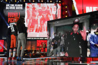 An image of Northwestern cornerback Greg Newsome II, right, is displayed onstage after he was chosen by the Cleveland Browns with the 26th pick in the first round of the NFL football draft, Thursday April 29, 2021, in Cleveland. (AP Photo/Tony Dejak)