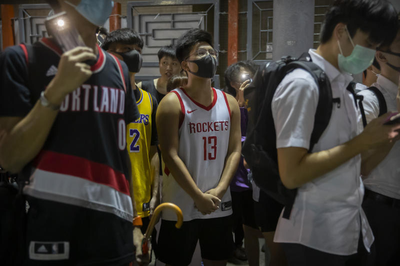 A demonstrator wearing a Houston Rockets jersey sings the U.S. national anthem with fellow demonstrators during a rally at the Southorn Playground in Hong Kong, Tuesday, Oct. 15, 2019. Protesters in Hong Kong have thrown basketballs at a photo of LeBron James and chanted their anger about comments the Los Angeles Lakers star made about free speech during a rally in support of NBA commissioner Adam Silver and Houston Rockets general manager Daryl Morey, whose tweet in support of the Hong Kong protests touched off a firestorm of controversy in China. (AP Photo/Mark Schiefelbein)