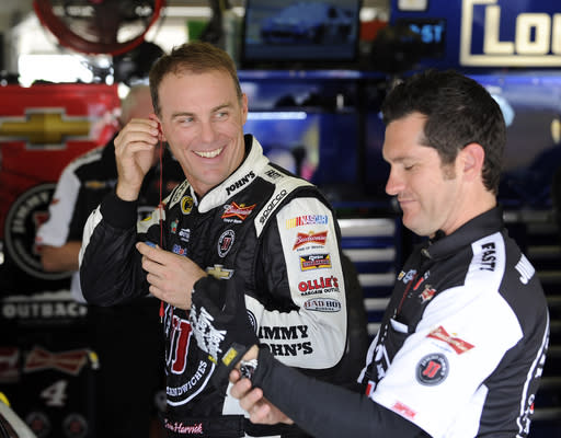 Sprint Cup Series driver and pole winner Kevin Harvick, left, smiles in the garage during practice for Sunday's NASCAR Sprint Cup Series auto race at Atlanta Motor Speedway, Saturday, Aug. 30, 2014 in Hampton, Ga. (AP Photo/David Tulis)