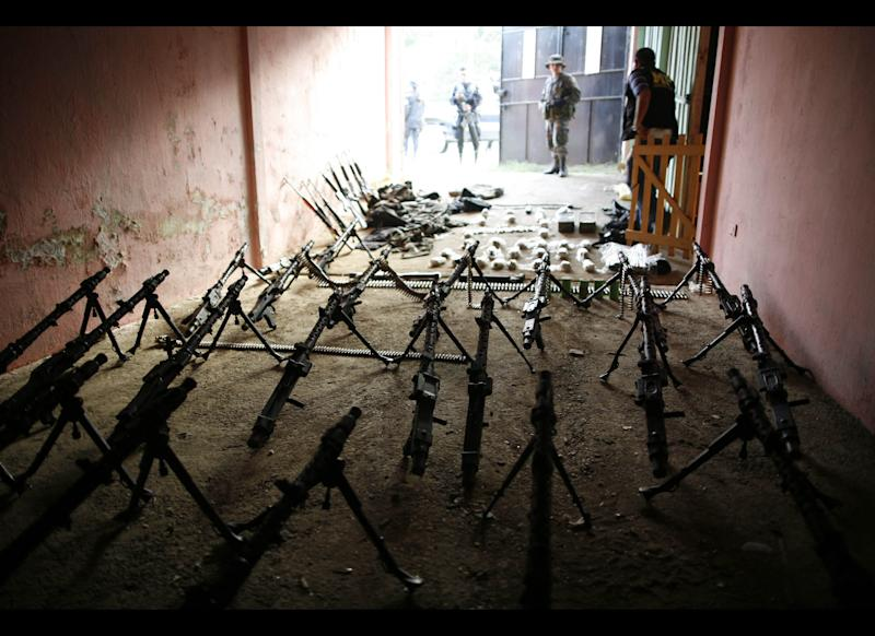 In this Dec. 21, 2010 file photo, weapons seized during a police and military raid are displayed in Coban, province of Alta Verapaz, Guatemala. In Dec. 2010, the Guatemalan military declared a month long state of siege in Alta Verapaz in hopes of reclaiming cities that have been taken over by Mexico's Zetas drug gang. (AP Photo/Rodrigo Abd, File)