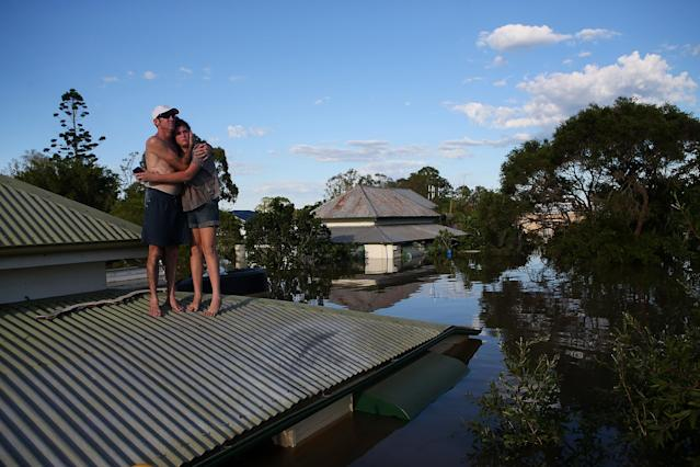 BUNDABERG, AUSTRALIA - JANUARY 29: A man comforts his daughter on their roof as they inspect damage to their neighbourhood as parts of southern Queensland experiences record flooding in the wake of Tropical Cyclone Oswald on January 29, 2013 in Bundaberg, Australia.Four deaths have been confirmed and thousands have been evacuated in Bundaberg as the city faces it's worst flood disaster in history. Rescue and evacuation missions continue today as emergency services prepare to move patients from Bundaberg Hospital to Brisbane amid fears the hospital could lose power. (Photo by Chris Hyde/Getty Images)
