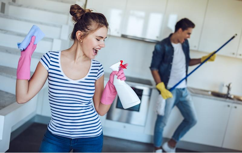 A man and a woman dancing while cleaning their house with gloves on.