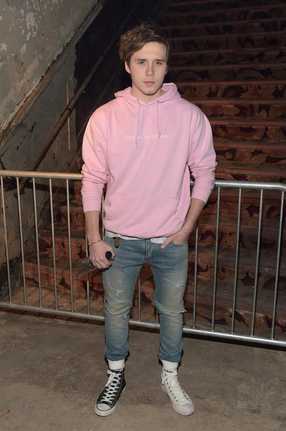 <p>Brooklyn Beckham went for a casual look in a pink hoody, jeans and mismatched Converse. <i>[Photo: Getty]</i> </p>