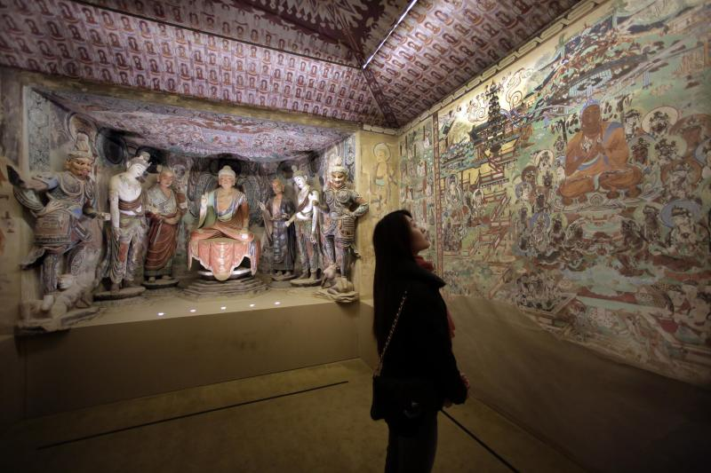 """A woman views a full scale replica cave from the 8th century that contains the Bodhisattva of the Mogao Caves, in """"Dunhuang: Buddhist Art at the Gateway of the Silk Road,"""" at the China Institute, in New York, Tuesday, April 24, 2013. (AP Photo/Richard Drew)"""
