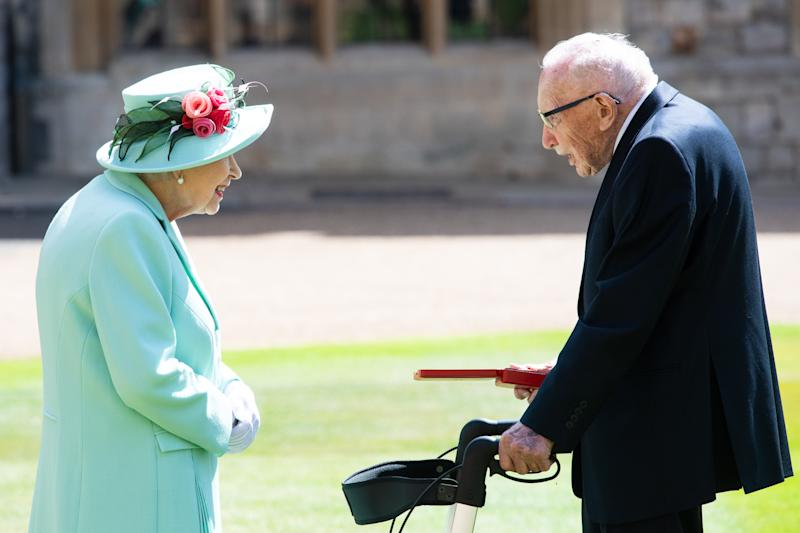 WINDSOR, ENGLAND - JULY 17: Queen Elizabeth presents the insignia of Knight Bachelor to Captain Sir Thomas Moore during an investiture ceremony at Windsor Castle on July 17, 2020 in Windsor, England. British World War II veteran Captain Tom Moore raised over £32 million for the NHS during the coronavirus pandemic. (Photo by Pool/Samir Hussein/WireImage)
