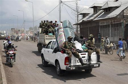 M-23 rebel fighters are seen on a vehicle as they withdraw from Goma