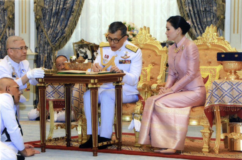 In this photo released by Bureau of the Royal Household ,Thailand's King Maha Vajiralongkorn Bodindradebayavarangkun, center, sits with Queen Suthida Vajiralongkorn Na Ayudhya as they sign their marriage certificates at Ampornsan Throne Hall in Bangkok, Thailand, Wednesday, May 1, 2019.Thailand's King Maha Vajiralongkorn, who will have his official coronation on Saturday, has appointed his consort as the country's queen. An announcement Wednesday in the Royal Gazette said Suthida Vajiralongkorn Na Ayudhya is legally married to the 66-year-old king, and is now Queen Suthida. (Bureau of the Royal Household via AP)