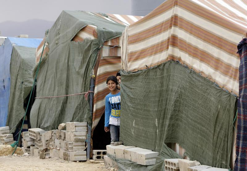 In this Tuesday, Oct. 2, 2012 photo, Syrian refugees girls appear through tents at a refugee camp in Arsal, a Sunni Muslim town eastern Lebanon near the Syrian border, has become a safe haven for war-weary Syrian rebels and hundreds of refugee families. Many in Arsal support the rebels, but the town's stand is risking heightened tensions with its Shiite Muslim neighbors in an area controlled by Hezbollah, a militia that backs the Syrian regime. Deepening sectarian rifts are one of the ways in which Syria's 18-month-old conflict is destabilizing an already volatile region. (AP Photo/Bilal Hussein)