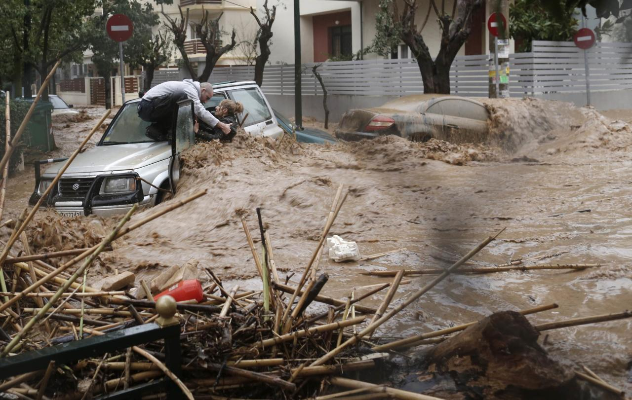 A woman is rescued from deadly floodwater by a man standing on top of her car during heavy rains in Athens, Greece (Reuters)