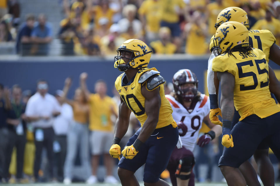 West Virginia linebacker Jared Bartlett (10) reacts after sacking Virginia Tech quarterback Braxton Burmeister (3) during the second half of an NCAA college football game in Morgantown, W.Va., Saturday, Sept. 18, 2021. (AP Photo/William Wotring)