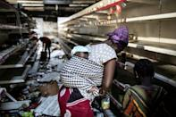 A woman picks up groceries at a looted supermarket in Dakar on March 6. The store was one of several owned by France's Auchan chain which were torched and pillaged during the unrest