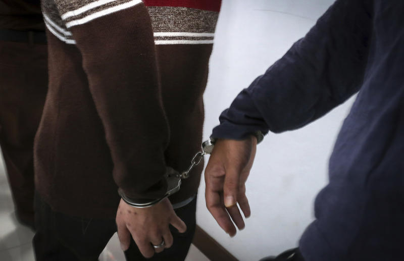 Two men accused of having gay sex are handcuffed as they arrive at the Shariah court in Banda Aceh, Indonesia, Wednesday, May 17, 2017. A Shariah court in Indonesia's conservative Aceh province has sentenced two gay men to public caning for the first time, further tarnishing the country's moderate image after a top Christian politician was imprisoned for blasphemy. (AP Photo/Heri Juanda)
