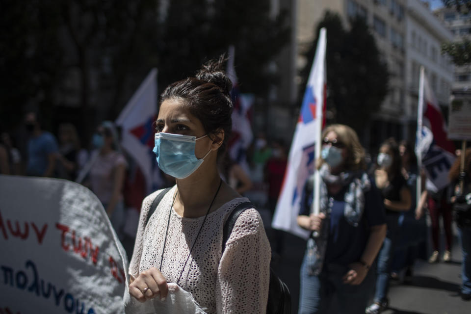 Greek state school teachers and students, wearing masks to prevent the spread of the coronavirus, protest in Athens, on Wednesday, May 13, 2020. Unions oppose government plans to allow remote teaching with use of a camera that will show the blackboard as part of the government's response to the coronavirus pandemic .(AP Photo/Petros Giannakouris)