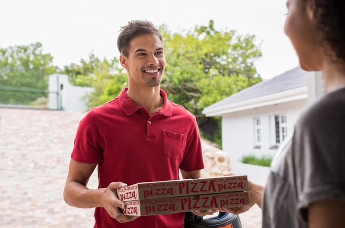 Smiling man handing two pizza boxes to a woman.