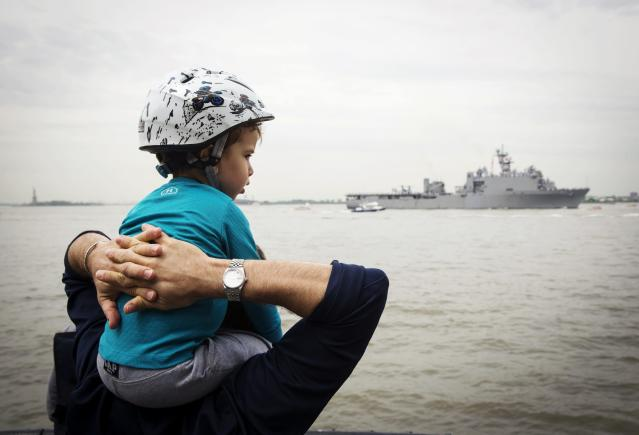A young boy sits on his father's shoulder in Battery Park as the USS Oak Hill, a Harpers Ferry-class dock landing ship of the United States Navy, arrives in New York Harbor for Fleet Week in New York, May 21, 2014. REUTERS/Lucas Jackson (UNITED STATES - Tags: SOCIETY MILITARY)