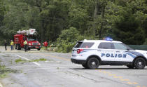 A crew works to remove a downed tree from blocking Route 138 in South Kingstown, R.I., Sunday, Aug. 22, 2021. Strong winds from Tropical Storm Henri toppled many trees in the southern regional of the state. (AP Photo/Stew Milne)