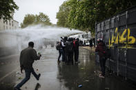 Police use a water canon to disperse protesters on the Place de la Nation during May Day march, Saturday, May 1, 2021 in Paris. Protesters, workers and union leaders demonstrated during slimmed down but still boisterous May Day marches on Saturday, demanding more labor protections amid the coronavirus pandemic. (AP Photo/Lewis Joly)