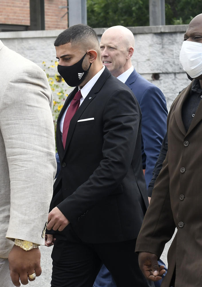 Nauman Hussain, left, who is charged with 20 counts of second degree manslaughter and criminally negligent homicide in the 2018 limousine crash, walks with his attorney Lee Kindlon at the Schoharie High School gymnasium Thursday, Sept. 2, 2021, in Schoharie, N.Y. (AP Photo/Hans Pennink)