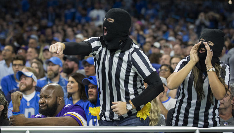 Minnesota Vikings fan Ryan Weche, of Boston, seated at left, and Detroit Lions fans Andrew DeHaan and his wife, Stephanie DeHann, of Detroit, react to a call in the second quarter of an NFL football game, Sunday, Oct. 20, 2019, in Detroit. (Jerry Holt/Star Tribune via AP)