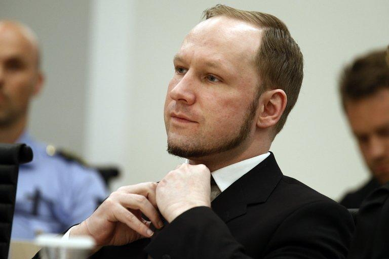 Self confessed mass murderer Anders Behring Breivik adjusts his tie  at Oslo District Court on August 24, 2012