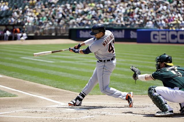 Detroit Tigers' Victor Martinez singles against the Oakland Athletics during the first inning of a baseball game Thursday, May 29, 2014, in Oakland, Calif. (AP Photo/Marcio Jose Sanchez)