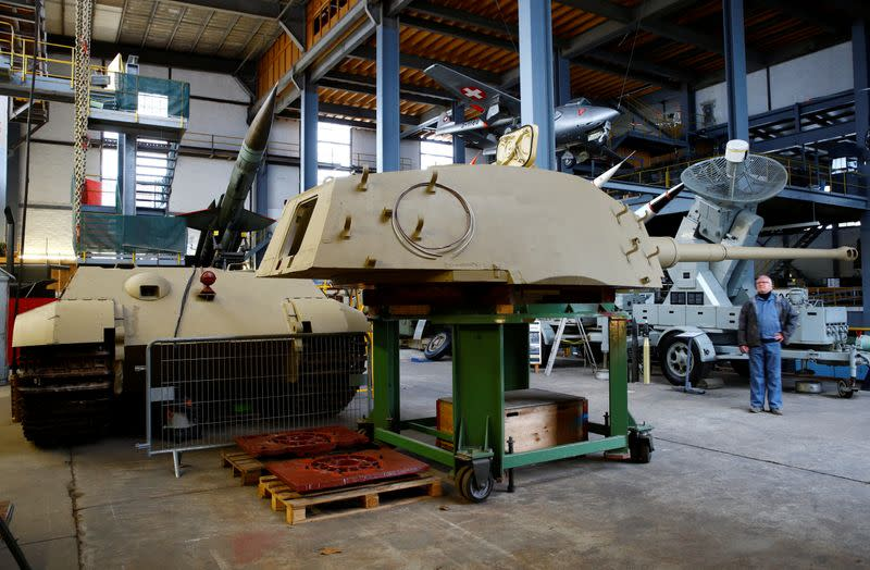"Kubicki stands in front of the turret of a German World War II Tiger II ""King Tiger"" tank during restoration works at Swiss Military Museum Full in Full"