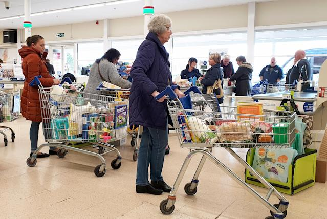 An elderly lady queues to pay for her shopping at a supermarket in Ashford, Kent, as UK, shoppers are emptying shelves as fears grow over the spread of the coronavirus. (PA)