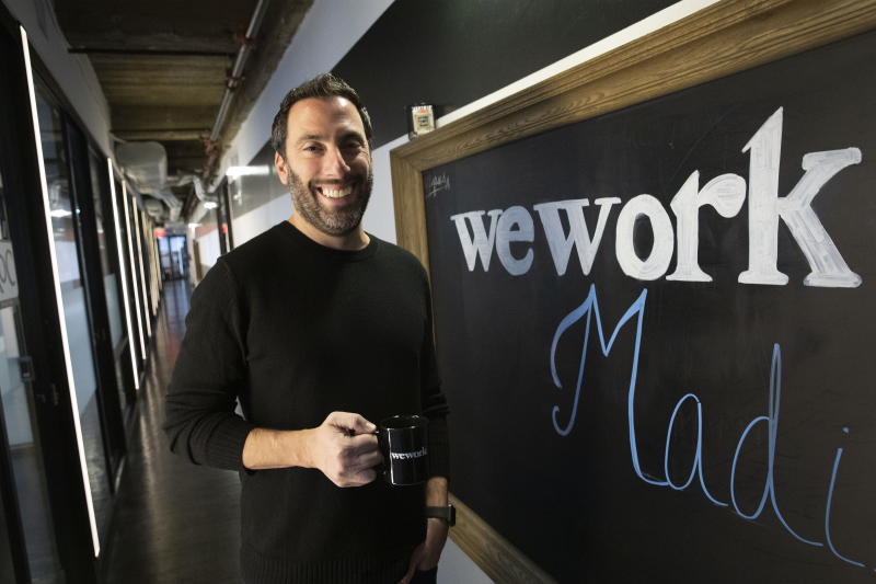 In this Tuesday, Nov. 5, 2019 photo, Lanny Grossman, owner of public relations firm EM50 Communications, poses at a WeWork office space near Grand Central station in New York.  Emptier than other WeWorks just blocks away, the space is sometimes dark because too few people show up to trigger enough automatic lighting sensors, Grossman said. The office-sharing company is slashing the lavish spending that fueled the office-sharing company's breakneck growth while racking up unsustainable losses that ultimately turned off Wall Street investors, forcing it to shelve its initial public offering.  (AP Photo/Mark Lennihan)